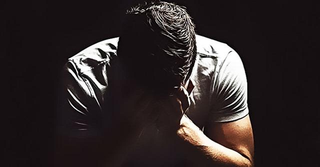 hombre-triste-preocupado-con-manos-en-el-rostro-fondo-oscuro
