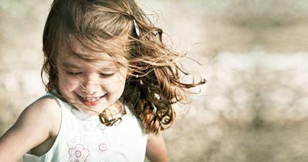 chica-nina-sonriendo-en-campo-felicidad-290616