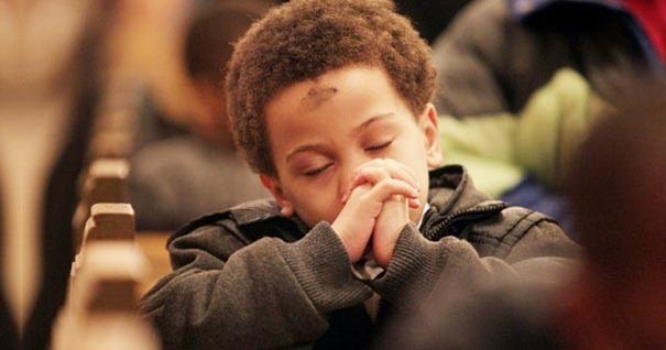nino-muchacho-rezando-sentado-miercoles-ceniza-cruz-frente-iglesia