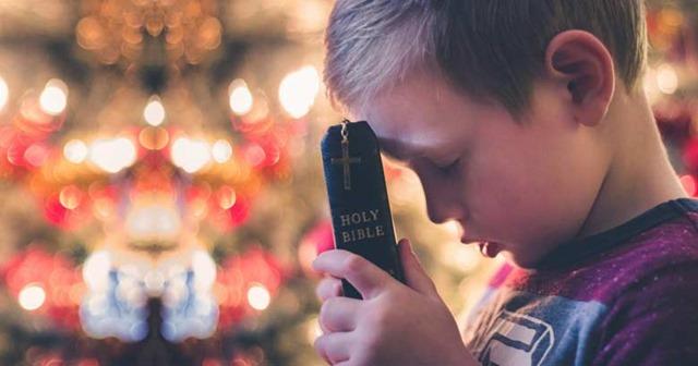 muchacho-orando-biblia-en-mano-crucifijo